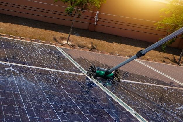 Operaio solare che pulisce i pannelli fotovoltaici con spazzola e acqua. pulizie fotovoltaiche. Foto Premium