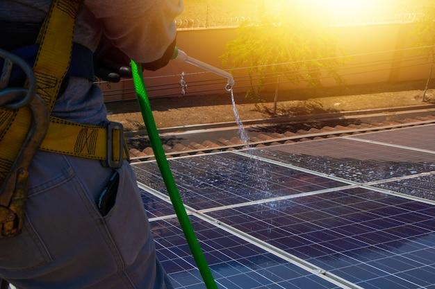 Operaio solare che pulisce i pannelli fotovoltaici con spazzola e acqua. pulizie fotovoltaiche.