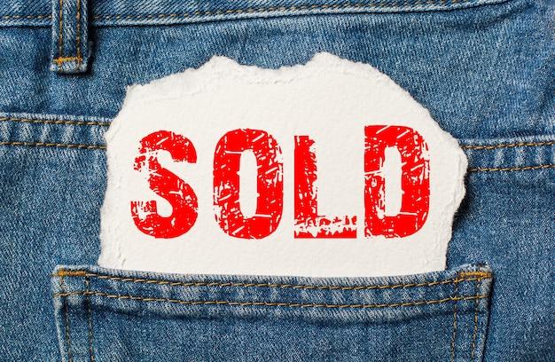 Venduto su carta bianca nella tasca dei jeans blu denim