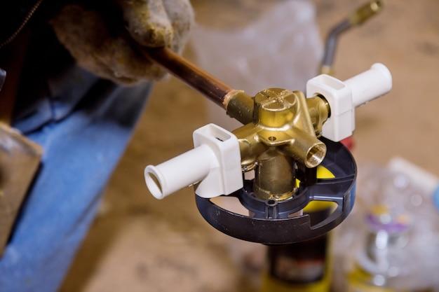 Raccordo a saldare in ottone su tubo di rame con torcia di saldatura su impianto idrico.