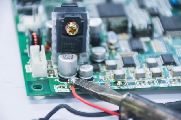Saldatura. macrofotografia. sensore tensore di saldatura sulla piastra. ingegneria microelettronica e concetto di tecnologia. il tecnico sta riparando il componente elettronico.