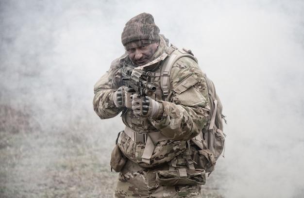 Soldato in uniforme mimetica, indossando munizioni militari, mirando i fucili di servizio, coprendosi a vicenda, sparando ai concorrenti, attaccando i nemici attraverso la cortina fumogena