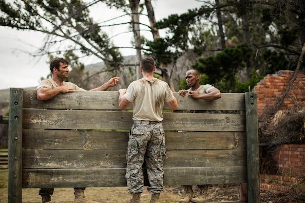Soldato che si arrampica sulla parete di legno nel campo di addestramento