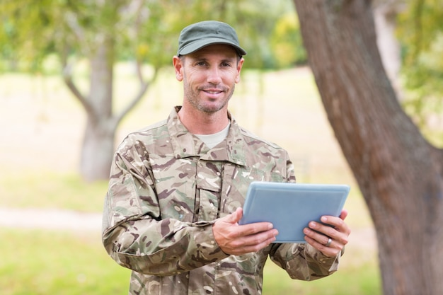 Soldato che esamina il pc della compressa nel parco