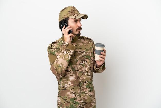 Uomo soldato isolato su sfondo bianco che tiene il caffè da portare via e un cellulare