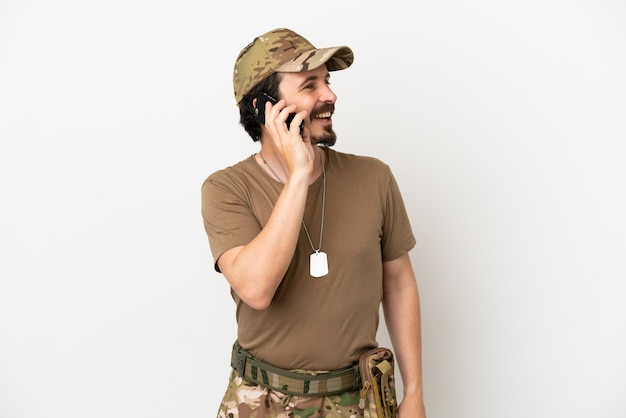 Uomo soldato isolato su sfondo bianco che tiene una conversazione con il telefono cellulare con qualcuno