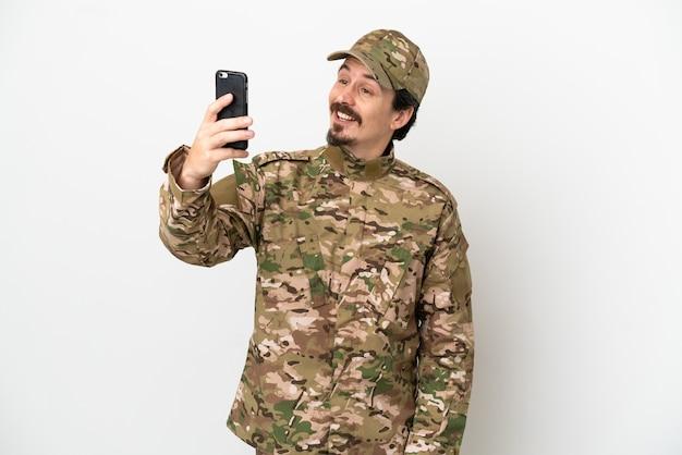 Uomo soldato isolato su sfondo bianco che fa un selfie