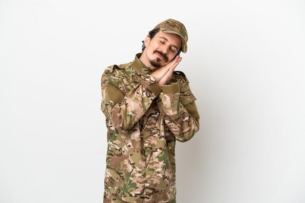Uomo soldato isolato su sfondo bianco che fa il gesto del sonno in un'espressione adorabile