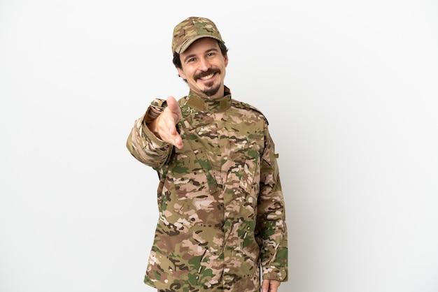Uomo soldato isolato su sfondo bianco che stringe la mano per aver chiuso un buon affare