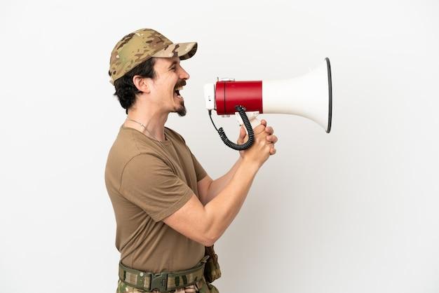 Uomo soldato isolato su sfondo bianco che grida attraverso un megafono