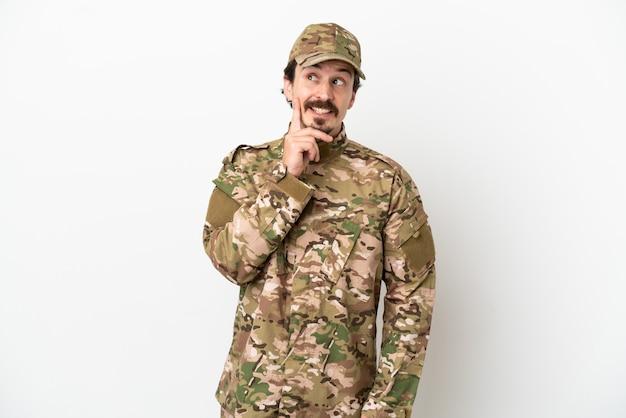 Uomo soldato isolato su sfondo bianco pensando a un'idea mentre guarda in alto