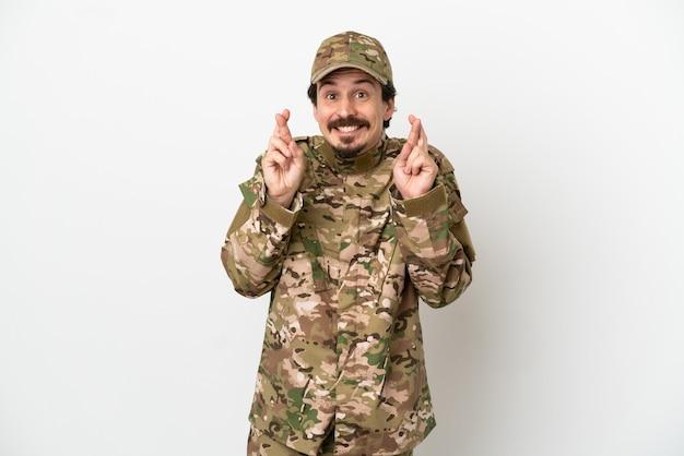 Uomo soldato isolato su sfondo bianco con le dita incrociate
