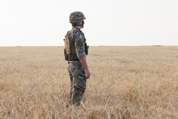 Uomo soldato in piedi contro un campo. ritratto di felice militare nel campo di addestramento. soldato dell'esercito americano nella missione. guerra e concetto emotivo.