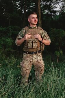 Uomo soldato in piedi contro un campo. ritratto di felice militare nel campo di addestramento. soldato dell'esercito americano in missione