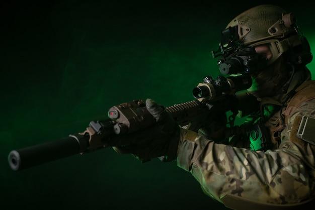 Il soldato in abiti militari con un dispositivo per la visione notturna e su uno sfondo scuro