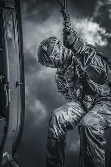 Il soldato si prepara a saltare da un elicottero. il concetto di giochi per computer. tecnica mista