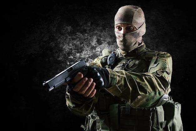 Il soldato dell'unità speciale in equipaggiamento completo mira al sospetto dalla pistola. tecnica mista