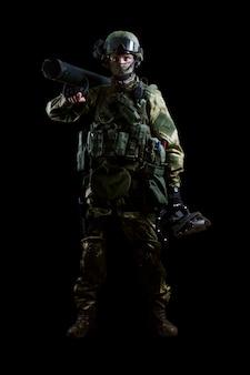 Il soldato dell'unità speciale sta in uniforme militare con un ariete sulla spalla e un dispositivo per aprire le porte. tecnica mista