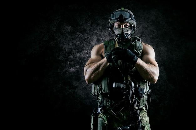 Il soldato dell'unità speciale sta con un'arma automatica a vantaggio. tecnica mista