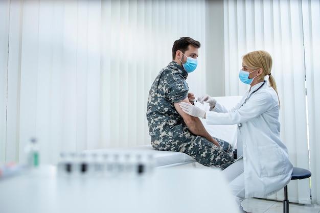 Soldato in uniforme che riceve il vaccino sparato contro il virus corona presso la clinica