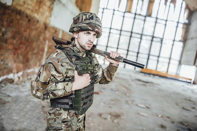 Un soldato in uniforme indossa un grosso fucile tra le mani.