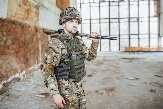 Un soldato in uniforme indossa un grosso fucile tra le mani