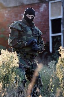 Il soldato con la pistola è all'aperto nella natura.