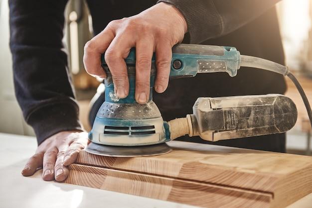 Solido come il legno con cui lavoriamo l'operaio macina il legno della rettificatrice angolare