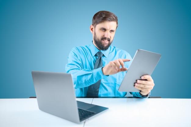 Un uomo solido in un ufficio davanti a un computer tiene un tablet in una mano e fa clic su di esso durante l'esecuzione di rapporti finanziari Foto Premium