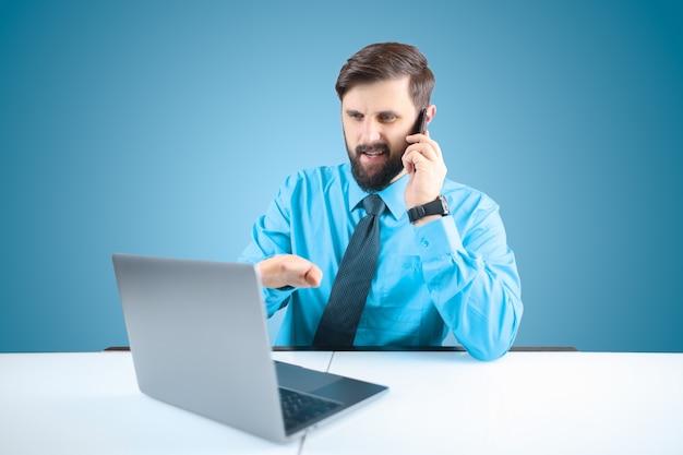 Un uomo solido in ufficio davanti al computer parlando al telefono e indicando il monitor del laptop con la mano