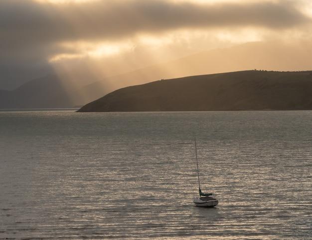 Barca solitaria che galleggia sull'acqua durante l'alba con raggi di luce sullo sfondo della nuova zelanda