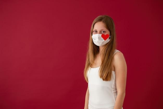 Giovane donna caucasica solitaria che sorride sotto la mascherina bianca con il segno rosso del cuore