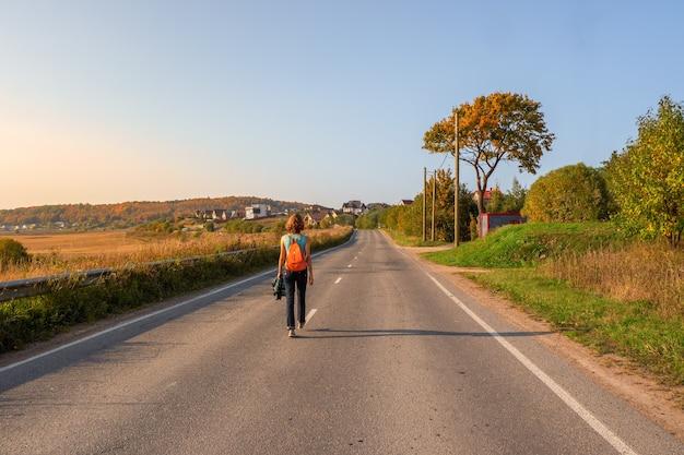 Concetto di viaggio da solista. vista posteriore della donna con lo zaino che cammina sulla strada campestre di autunno, viaggio escursionistico.