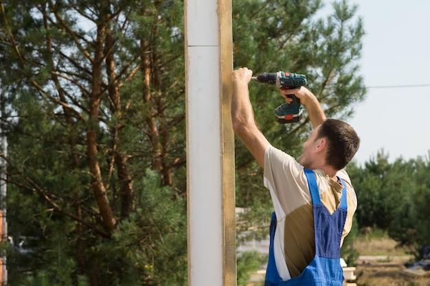 Solo giovane uomo di costruzione che utilizza il dispositivo trapano cordless nella costruzione di una casa