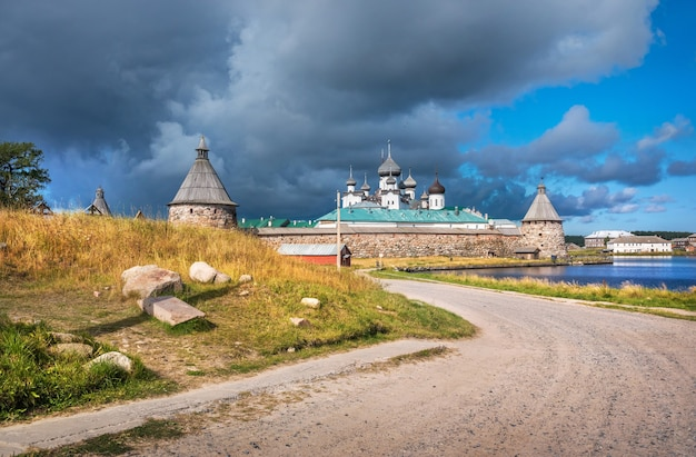 Monastero di solovetsky dal lato del lago santo e la strada sotto i raggi del sole autunnale