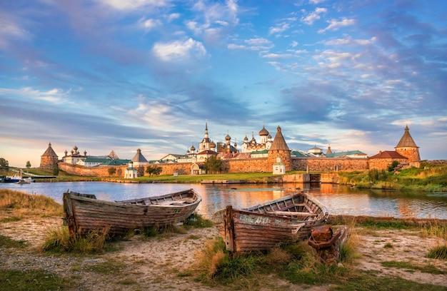 Monastero di solovetsky sulle isole solovetsky, l'acqua blu della baia della prosperità e vecchie barche di legno sulla riva