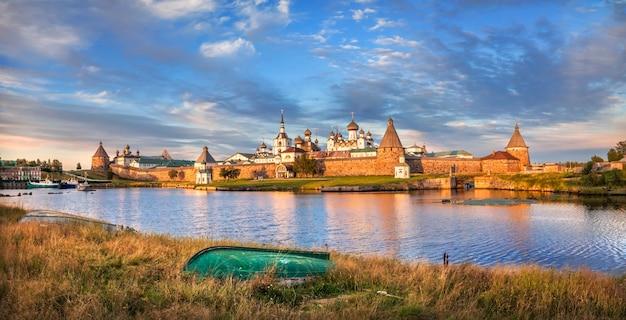 Monastero di solovetsky sulle isole solovetsky, l'acqua blu della baia della prosperità e una barca rovesciata