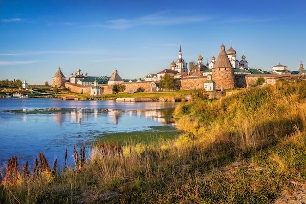 Monastero di solovetsky ed erba gialla di autunno sulla riva della baia di prosperità sotto i raggi del sole al tramonto