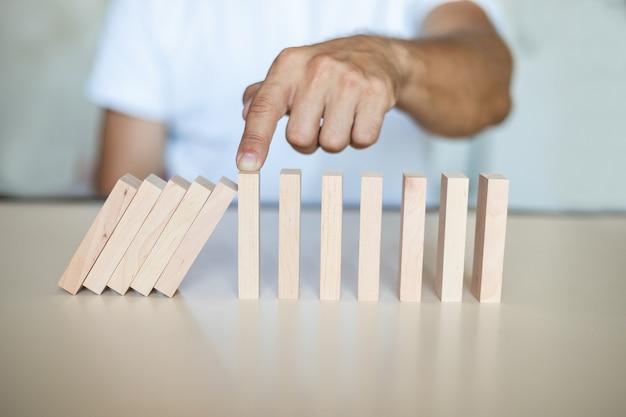 Concetto di soluzione con la mano che impedisce ai blocchi di legno di cadere nella linea del domino
