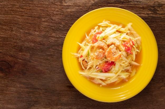 Som tum thai, som tam thai, cibo tailandese, insalata di papaya piccante con pomodoro, lime e peperoncino con gamberi essiccati su fondo in legno naturale, vista dall'alto