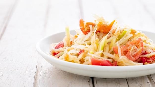 Som tum thai, som tam thai, cibo tailandese, insalata di papaya piccante con pomodoro, lime e peperoncino con gamberi essiccati su sfondo bianco in legno vecchio, fotografia di cibo leggera e ariosa