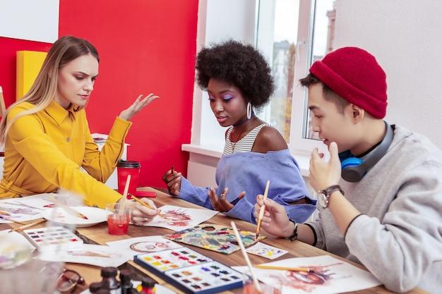 Alcuni argomenti. tre studenti di arte creativa alla moda che hanno alcuni argomenti mentre lavorano insieme