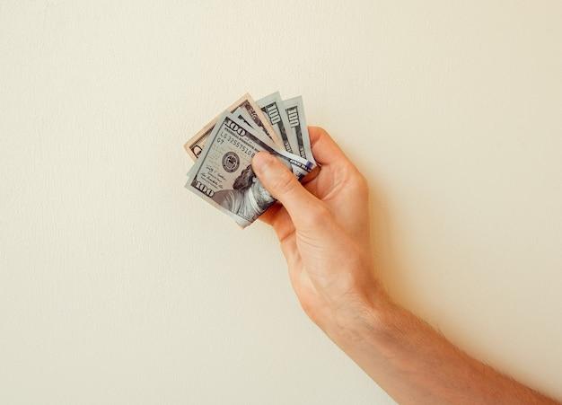 Alcune banconote da 100 dollari in mano di un uomo su uno sfondo solido. primo piano su sfondo stucco