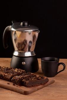 Alcune fette di brownie su legno, una caffettiera e una tazza di caffè.