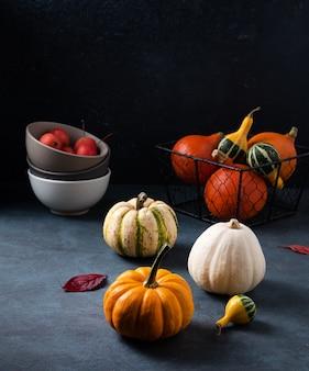 Alcune zucche decorative colorate e foglie di autunno sul tavolo scuro