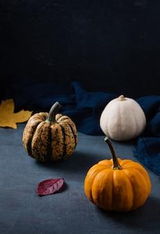Alcune zucche decorative e foglie di autunno sul tavolo scuro con tovagliolo