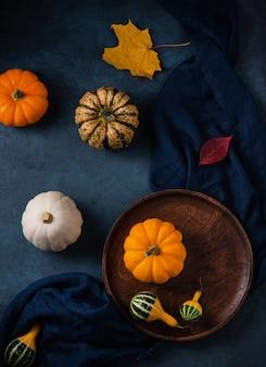 Alcune zucche decorative sul piatto di legno marrone e sulla tavola scura con il tovagliolo