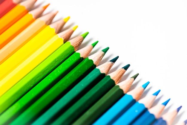 Alcuni pastelli a matita in legno colorati differenti disposti in una riga davanti a uno sfondo bianco isolato