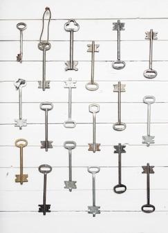 Alcune chiavi della porta allineate sulla vecchia superficie in legno, sullo sfondo del concetto di sicurezza e protezione.
