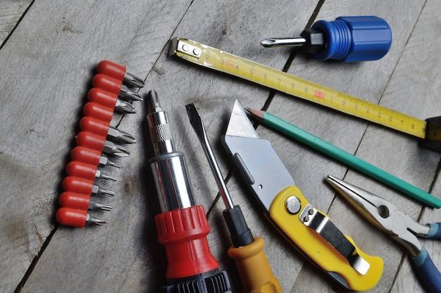 Alcuni strumenti di riparazione domestica si trovano su uno sfondo di legno. avvicinamento.